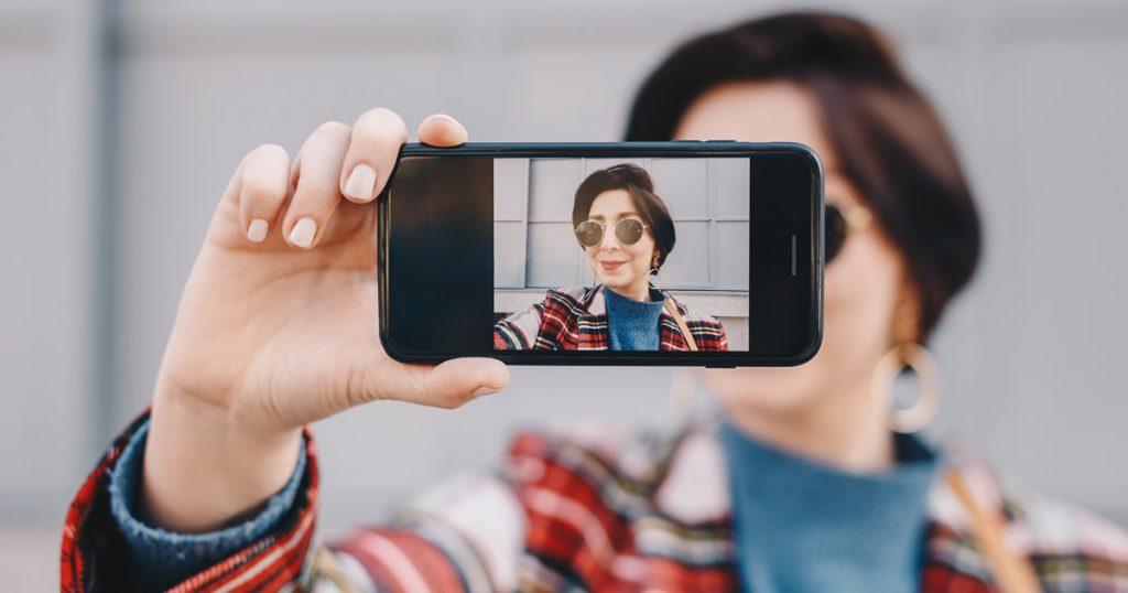 ragazza che si scatta un selfie da pubblicare sui social media