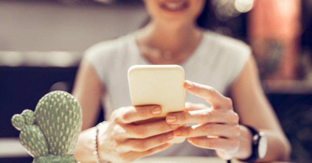 ragazza con smartphone che evita contenuti da non postare sui social.
