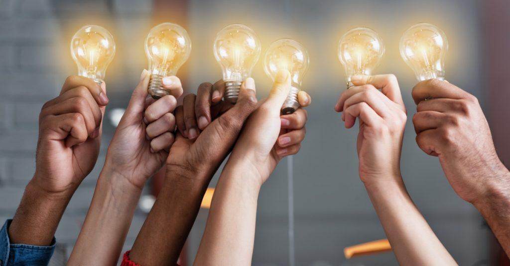 mani con lampadine per idee di successo
