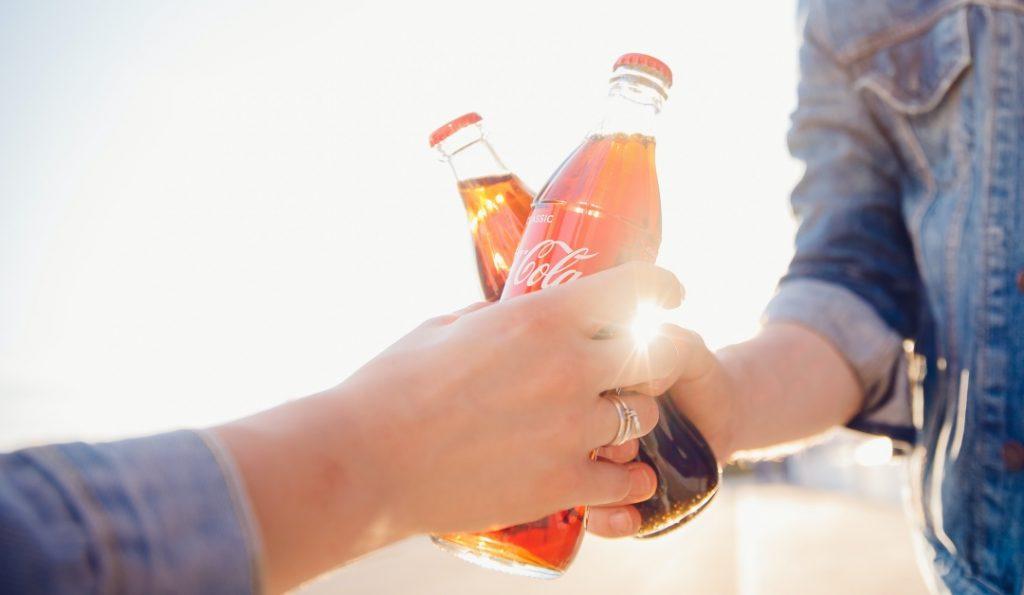 ragazze che brindano con bevande del brand coca-cola