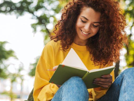 ragazza che legge libri per imparare a scrivere storie memorabili